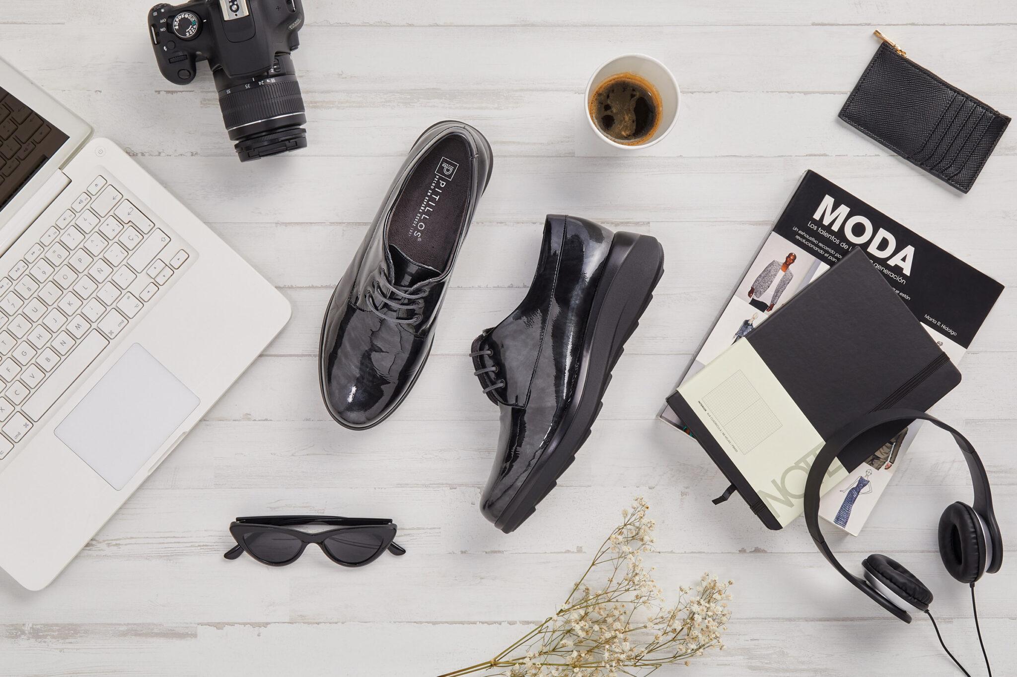 Bodegón: zapatos, auriculares, café. Sobre tarima clara