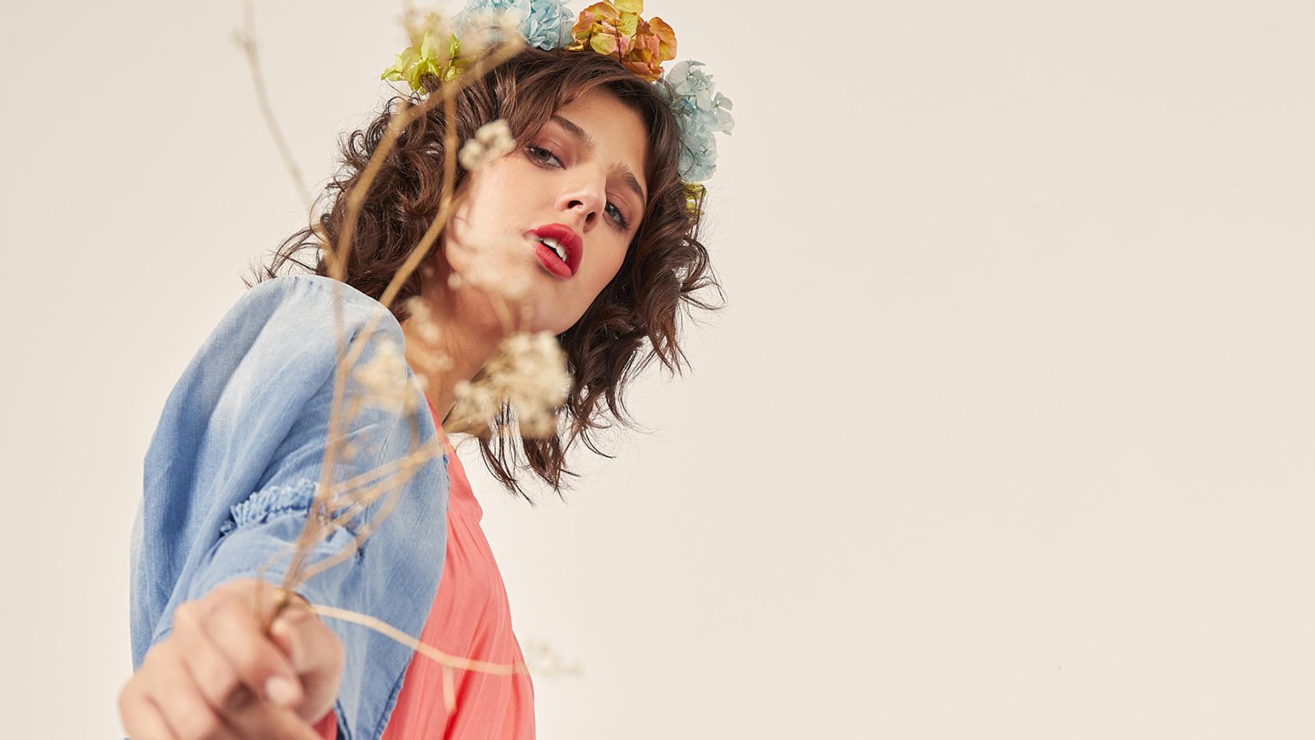 mujer con corona de flores paseando con trigo en la mano